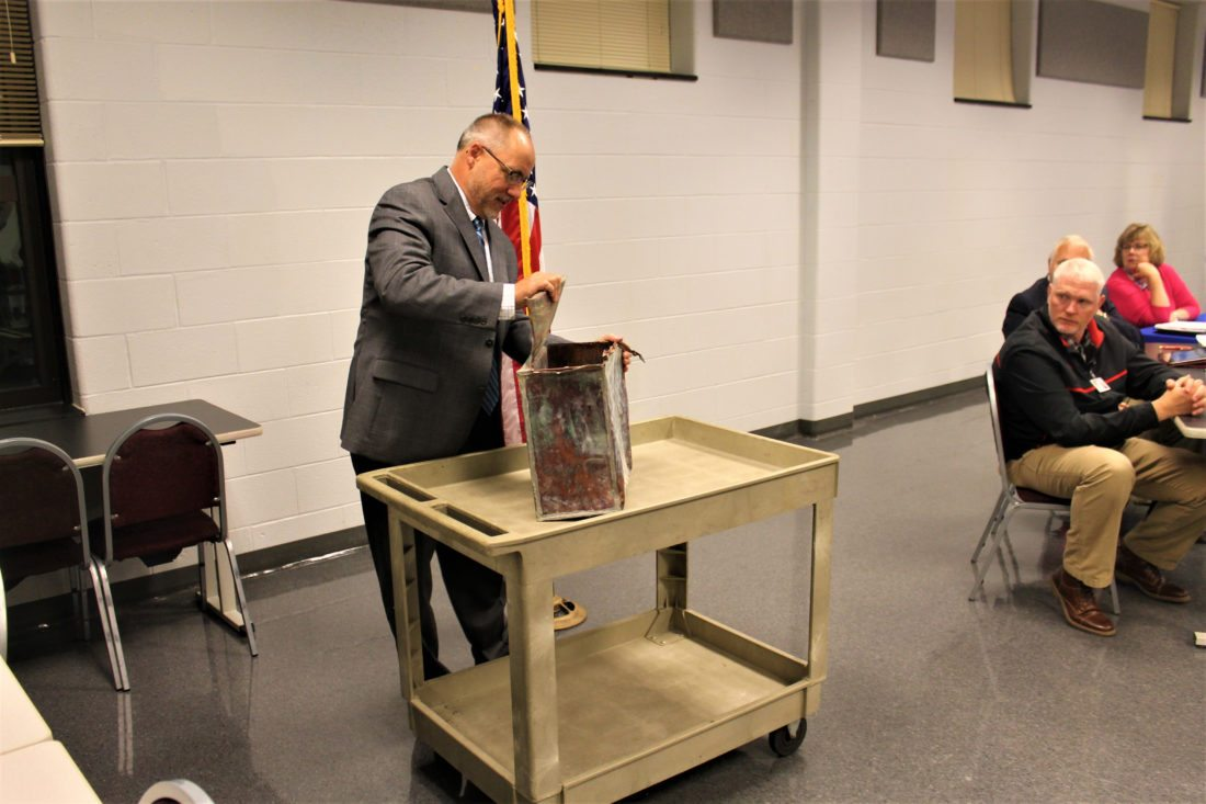 OBSERVER Photo by Jordan W. Patterson Superintendent Chuck Leichner opened a time capsule from 1939 this week during a meeting of the Cassadaga Valley Central School Board. The capsule was unearthed due to renovations taking place at the school.