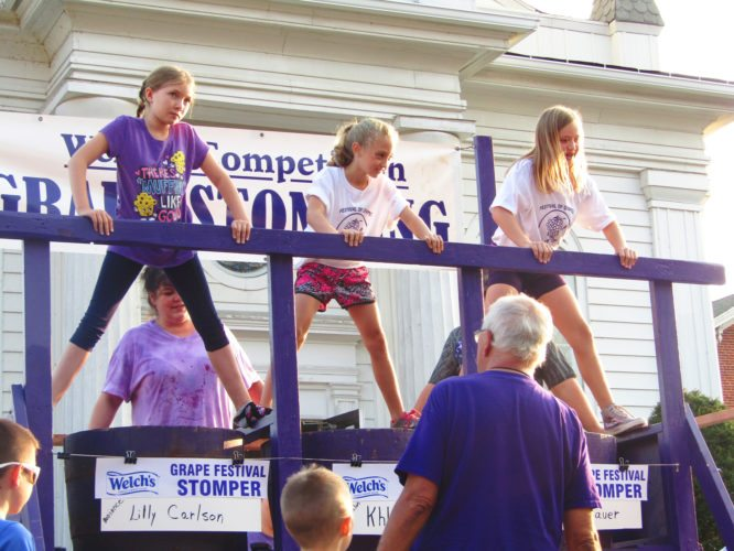 OBSERVER Photo by Greg Fox From left, Lilly Carlson, Khloe Karnes and Kimberly Bauer ready themselves during one of the heats at the Welch's grape stomping competition Friday, the first day of the 50th annual Festival of Grapes, in Silver Creek.