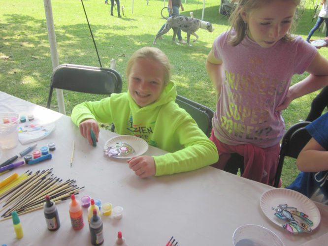 OBSERVER Photo by Diane Chodan Eva Williams, 8, flashes a smile as she works on her sun catcher at Harvest Chapel's family picnic. Craft activities included painting rocks, painting sun catchers and filling small bottles with different colored sands.