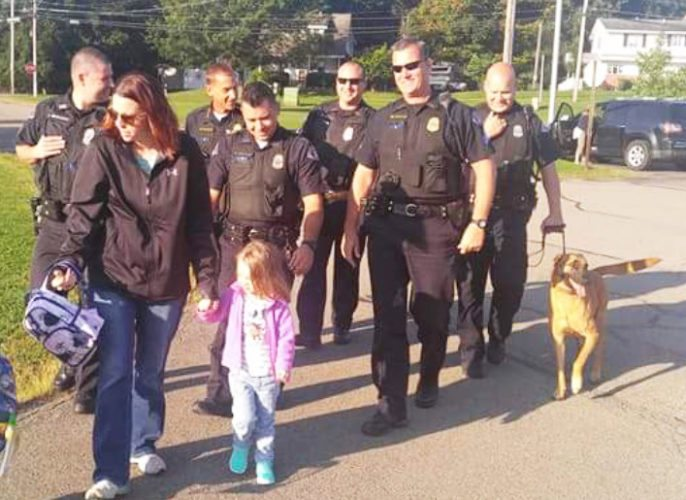 """Dunkirk police officers walk to school with Jennifer Hazelton and her daughter, Ava, last week in Ava's first day of preschool. Matthew Hazelton, husband and dad, was a member of the Dunkirk police force until he died in August. The officers' presence was part of the unit's promise to """"always be DPD Strong!"""""""
