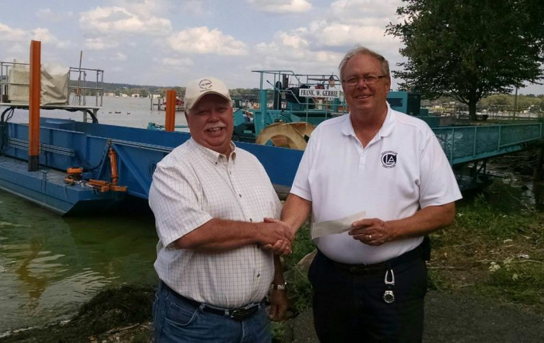 Submitted Photo: Mark Damon, left, of the CLFA presents Doug Conroe, right, of the CLA with a $7,000 donation for on-going lake cleanup efforts.