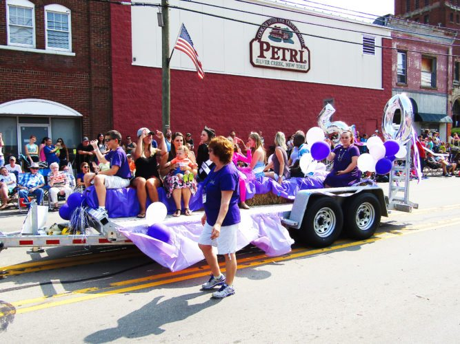 """OBSERVER Photo by Greg Fox The Festival of Grapes board and past pageant winners travel down the parade route Sunday with a big balloon """"50"""" for the festival's silver anniversary in Silver Creek."""