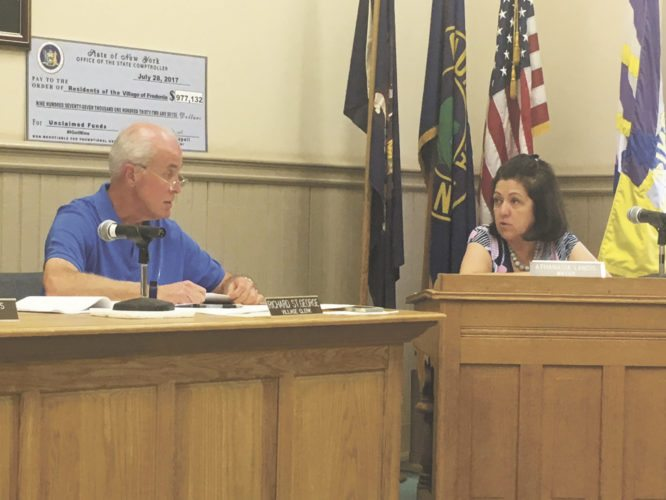 Fredonia Village Clerk Richard St. George, left, speaks with Fredonia Mayor Athanasia Landis during Monday's village board meeting.