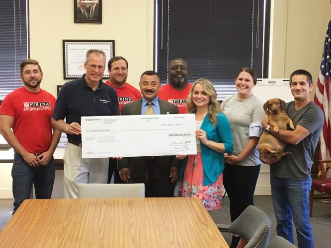 Submitted Photo: Dunkirk Mayor Willie Rosas holds a $10,000 check from Purina with Purina Plant Manager, Ron Bowers, left, and Monica Kemp, dog park advocate. They are joined by members of the Purina staff and Development Director Rebecca Yanus.