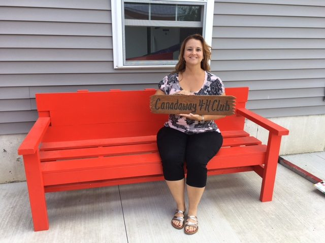 Heather Lesch, leader of the Canadaway 4-H Club, is seated on the bench her son Jacob made for his woodworking project.