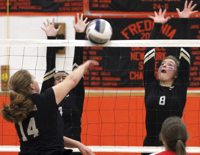 OBSERVER Photo by Lisa Monacelli Anna Valone (14) of Fredonia tries to hit around a double block put up by Nia Nephew and Krystal Schwab (8) of Silver Creek during Monday's CCAA North girls volleyball contest.