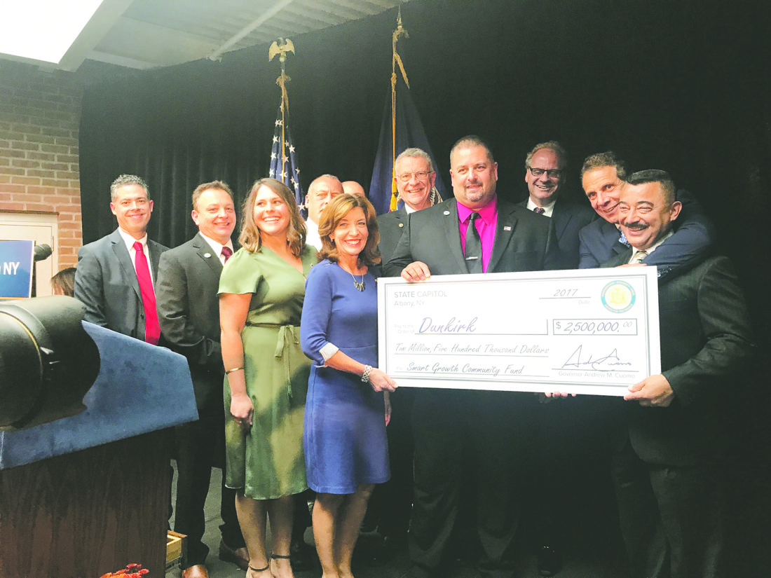 OBSERVERPhoto by Andrew David Kuczkowski At top left, city officials stand with New York Gov. Andrew Cuomo, back right with arm around Dunkirk Mayor Willie Rosas, and Lt. Gov. Kathy Hochul, holding check on left. The city was awarded $2.5 million toward improving its pier and waterfront.
