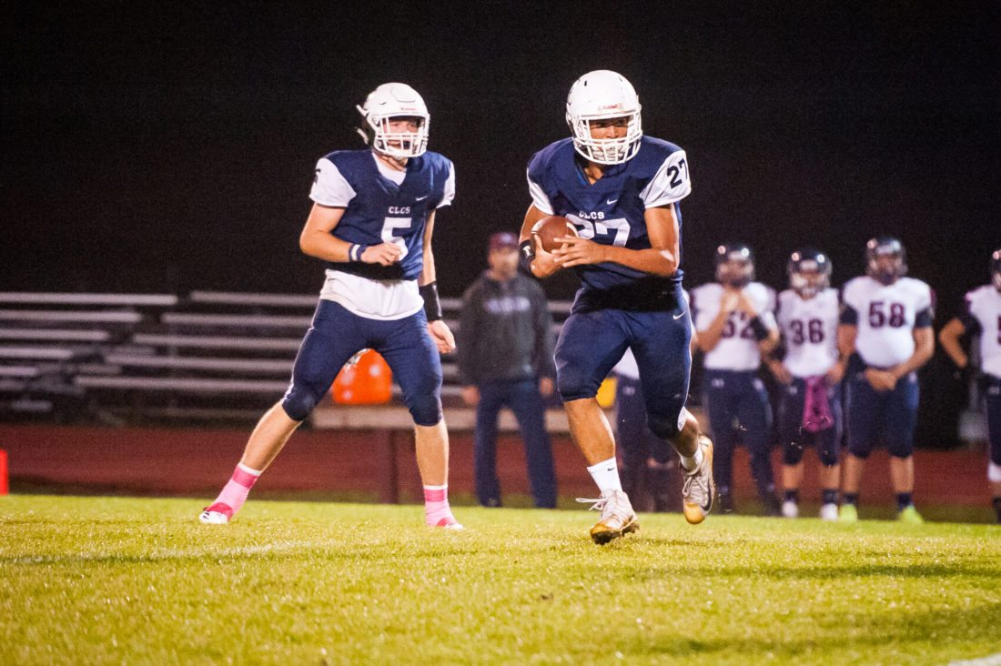 Photo by Valory Isaacson The Thunderbirds' Joshua Walsh carries the ball after taking the handoff from Devin Pope (5) during Friday's game in Mayville against Franklinville.