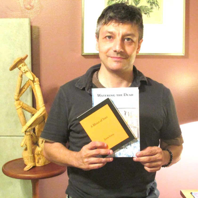 """OBSERVER Photo by Damian Sebouhian: Jason Irwin stands in front of a sculpture of Don Quixote, holding two of his published books of poems """"A Blister of Stars"""" (2016) and """"Watering the Dead"""" (2008). Look for his fifth collection of poems to be published sometime in the middle of next year."""