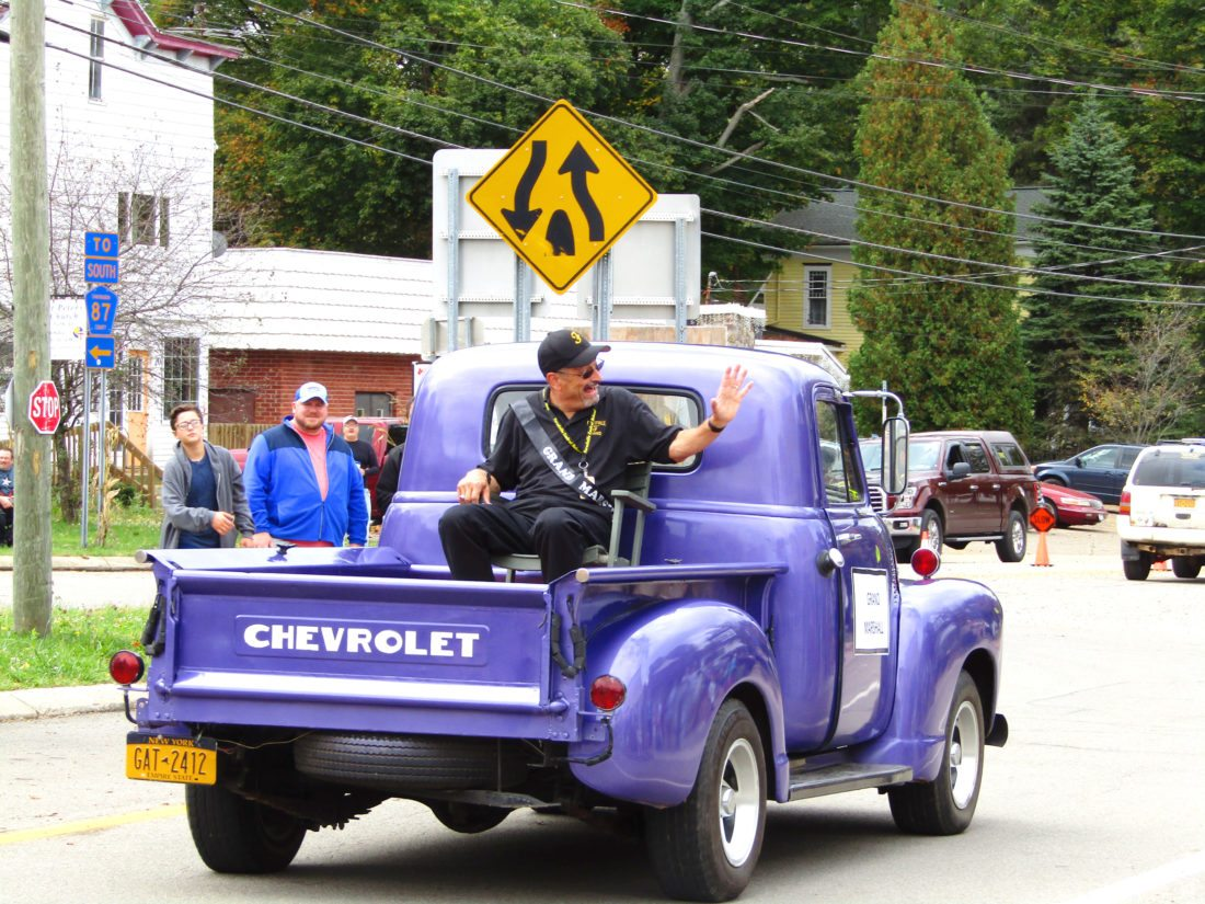 Photo by Greg Fox Parade Grand Marshal Jeff Geblein, longtime band director at Forestville school, was chauffeured in the back of Sarah Lomanto's purple Chevy truck at the Fall Festival Sunday.