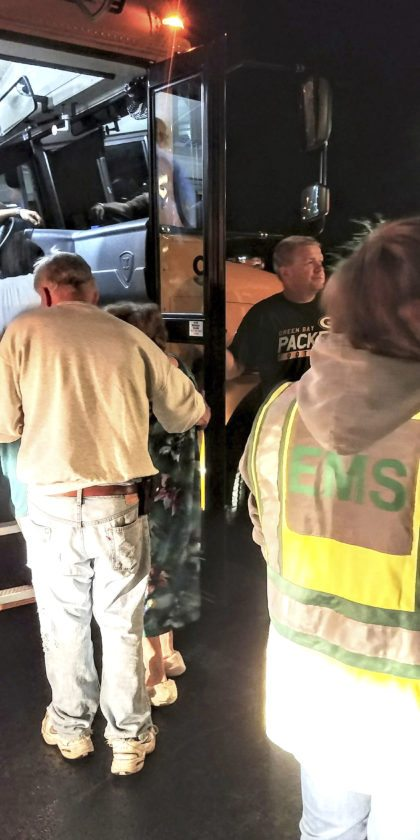 Submitted Photo: Dave Hazleton, left, and Steve Smith, at right, assist residents of the Herbert Star Apartments into a school bus as they were transported to safety at Brocton Central School, during a full scale evacuation still recently.