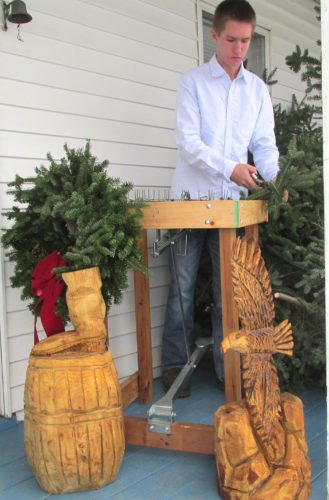 OBSERVER Photos by Damian Sebouhian Jimmy Keller stands with his homemade wreath making machine he designed himself, a finished wreath and two recent chainsaw carvings. Keller will be selling his art this weekend, Nov. 25-26 and next weekend, Dec. 2-3 at Smith's True Value in Irving.