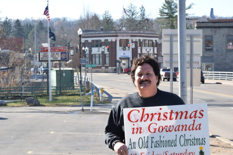 OBSERVER Photo by Andrew David Kuczkowski Gowanda Chamber of Commerce Nick Crassi stands outside of the village hall holding one of many Christmas in Gowanda signs. Christmas in Gowanda begins Friday, Dec. 1 with an array of events displaying the unique assets the village has to offer.