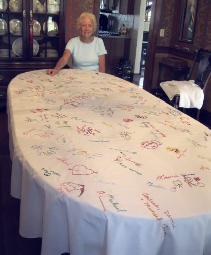 Shirley Erbsmehl displays the plain white tablecloth that is almost completely filled with hundreds of signatures and distinctive drawings placed there by people who have dined at their home since 1978.