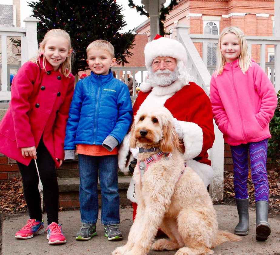 OBSERVER Photo by Tonja Dodd: The Beach children of Fredonia and their dog pose with Santa at the Miracle on Main Street festival in Fredonia Saturday. From left, Ella, Ethan, Santa, dog, Lollie, and Lily.