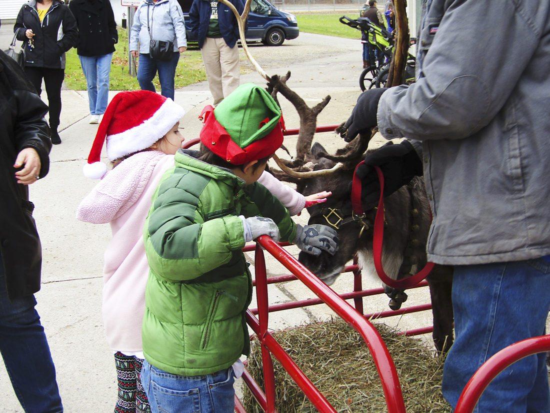 OBSERVER Photo by Greg Fox: Children gather around one of reindeer, Dancer.