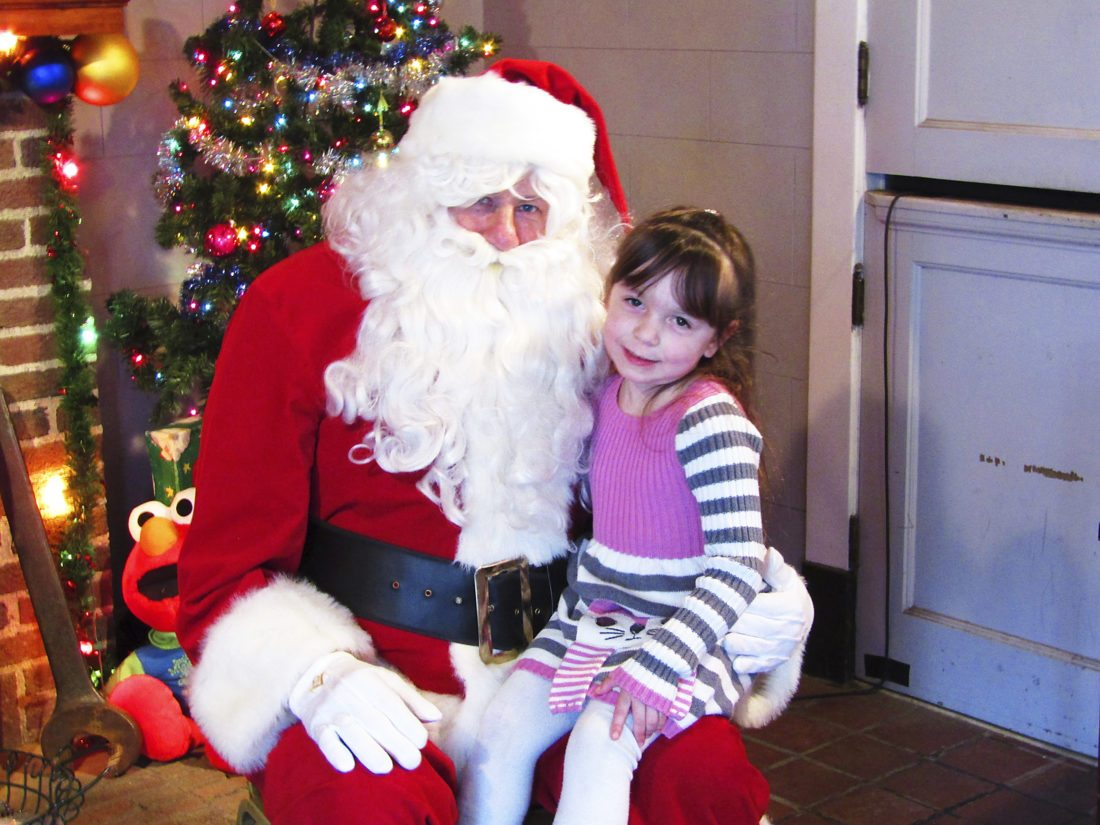 Four-year-old Lacey Fadale poses with OBSERVER Photo by Greg Fox: Santa Claus after telling him what she wants for Christmas.