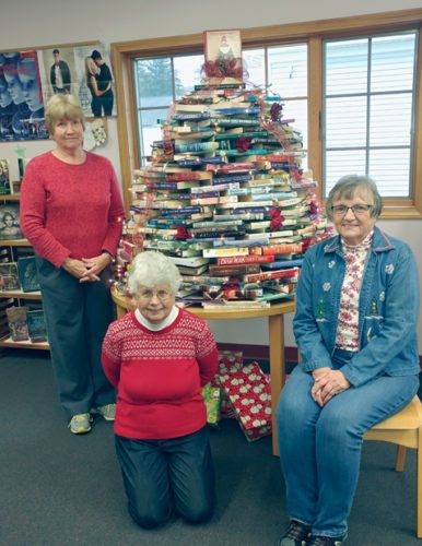 Submitted Photo The Sinclairville Free Library invites the public to visit the library this holiday season and admire the Christmas tree constructed with books and enjoy the following activities: Christmas Card Craft Class on Thursday, Dec. 14 at 5:30 p.m. This class is for ages 12 and up and will be led by library volunteer Sue Allenbrand. Pre-registration is required, and a fee of $2 per card will be charged for materials. Contact the library by calling 962-5885 or by email at sincfrlb@gmail.com to register for the class. Holiday Crafts with library volunteers Cheryl Swart and Peggy Minckler today from 4 to 5 p.m. (children under 8 must be accompanied by a caregiver) and Teen Game Night on Thursday, Dec. 21 from 5:30 to 7 p.m. Information about library programs and services is available on the library's new website at www.sinclairvillelibrary.org. Pictured are long time library volunteers who put together the book tree each year: left to right: Catherine Obert (winner of the Chautauqua-Cattaraugus Library System's 2016 Above & Beyond Award for Outstanding Volunteerism), Ainsley Smith and Karyn Okerlund. The library is located at 15 Main St. in Sinclairville.