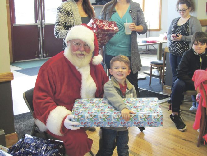 Zane Moore gets a gift from Santa at the Northern Chautauqua Conservation Club