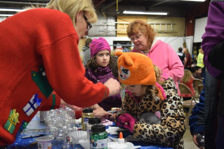 Volunteer Cathy Higgs, left in red, helps Julianna Wieczorek, 6, with decorations at the Forestville Fire Hall.