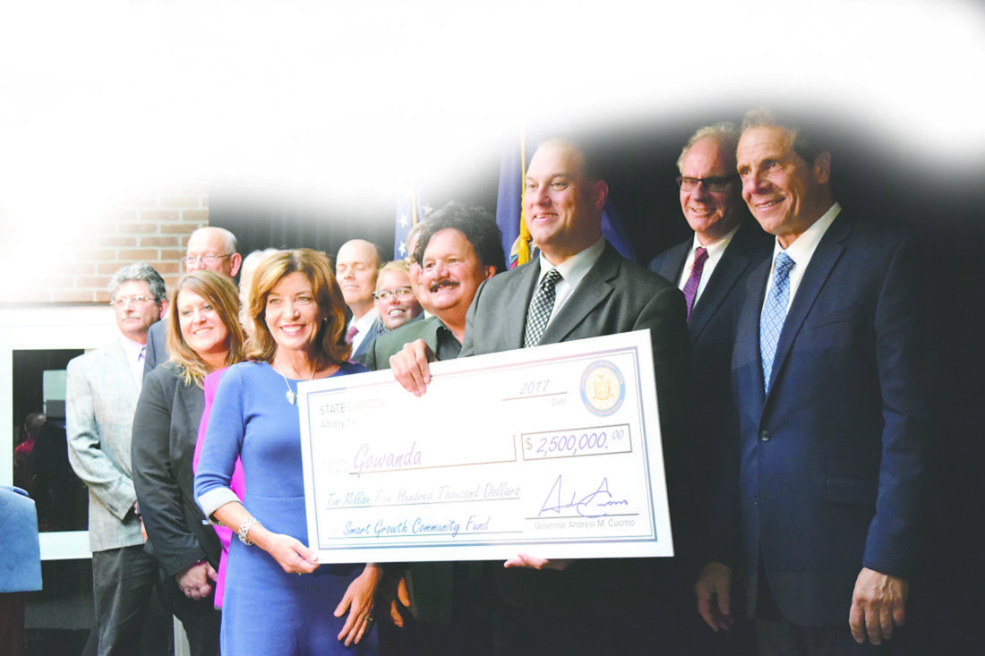 OBSERVER File Photo Gowanda Mayor David Smith stands in the center holding a $2.5 million check for the village of Gowanda as Lt. Gov. Kathy Hochul is to his left at the end of the check and Gov. Cuomo is at the right at the Oct. 4 event.