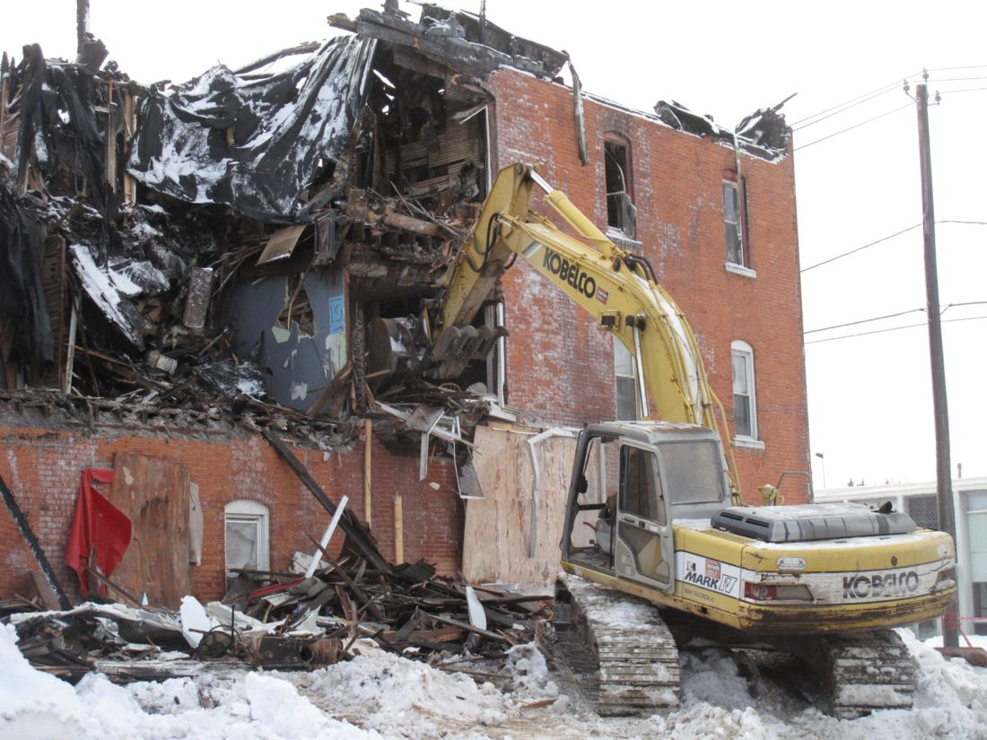 Photo by Katrina Fuller Brian Nelson, owner of 15 W. Main St. and the Falconer Vac Shop, and others watched as demolition began on his building on Wednesday afternoon. Nelson owned the building for 30 years, but was involved with it in some way for the past 48 years.