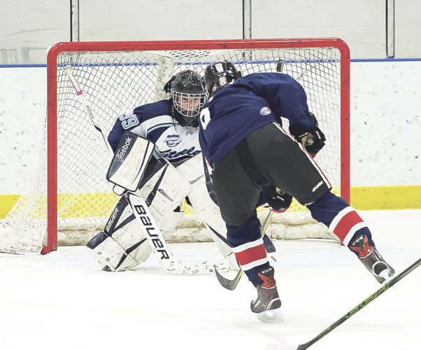 Steelers' goalie Gabriel Persch (99) makes tough one-on-one save against free-skating Andrew Sarafin (6) of East Aurora-Holland.