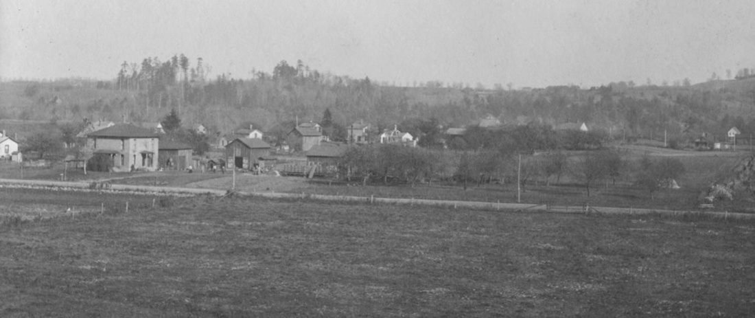 This is a photo of the Hidi section of Gowanda around 1900. The brick house at 174 Broadway still stands. Frederick Kenngott had a cider mill there.  You can see his apple orchard. Frederick Street, named after him, was built later on the right in this photo.