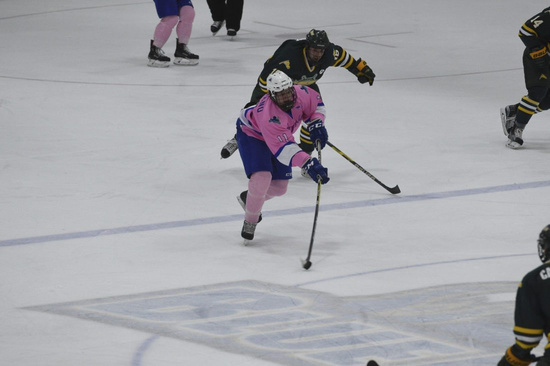 """Photo courtesy of the State University of New York at Fredonia Fredonia's Sam Wilbur (11) advances the puck while pursued by Oswego's Tyson Bruce during college hockey action Saturday at Steele Hall. The game was Fredonia's annual """"Pink the Rink"""" game honoring cancer survivors and raising money for cancer research."""