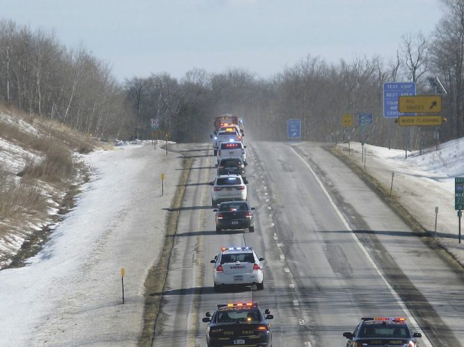 Photo by Eric Tichy Chautauqua County Sheriff's Office cruisers began escorting the hearse carrying deputy Michael Seeley, 44, near I-86 in Findley Lake Monday afternoon. Seeley, who gained widespread praise in 2013 for helping to save the life of a man and known for his career in emergency services, died Friday night at the Cleveland Clinic following a brief battle with leukemia.