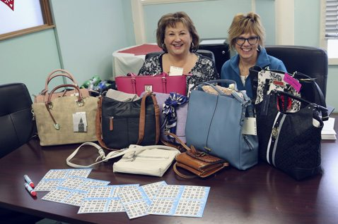 "Submitted Photo Pictured with the handbags that will be given away as prizes at the second annual Sassy Baggs & Beyond ""Blingo"" are Donna Germain, left, the owner of The Main Landing, and event organizer Victoria Trass Bardo."