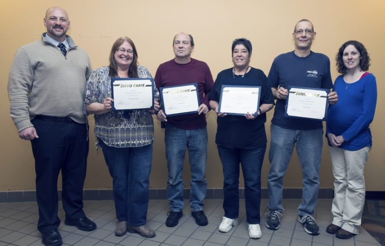 Submitted Photo Displaying their Custodial Safety Incentive Award certificates are (beginning second from left): Mary Ann Wykstra, Iris Rosa, Jack Anderson and Charles Miller, along with Mark Delcamp, assistant director of Custodial Services (far left) and Sarah Laurie, director of Environmental Health, Safety and Sustainability (far right).