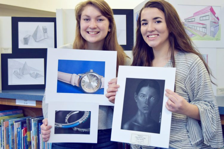 Submitted Photo Senior Krystle Schwab, left, and sophomore Chloe Vecchio show off some of their artwork amid the bookcases at the Anderson-Lee Library in Silver Creek.