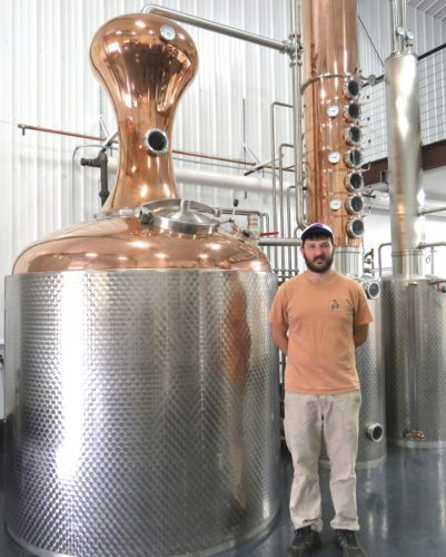 People who enjoy drinking a quality whisky or vodka now have the chance to taste test a unique apple vodka, a corn vodka and a corn whisky at the Ellicottville Distillery. Shown is Distiller Bryan Scharf with the 500-gallon copper pot still that was custom-made in Germany.  P-J photo by Deb Everts