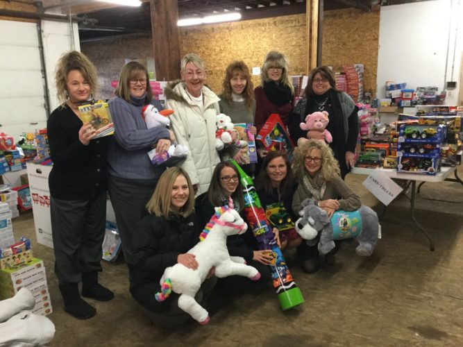 Employees of The Resource Center and Weber Knapp — Toys for Tots are pictured.