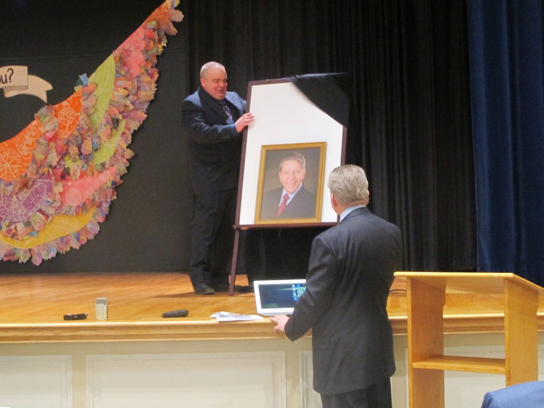 Jamestown School Board President Paul Abbott, left, presents Superintendent Tim Mains with a portrait. Tuesday's meeting was Mains' last with the school district. P-J photo by Katrina Fuller