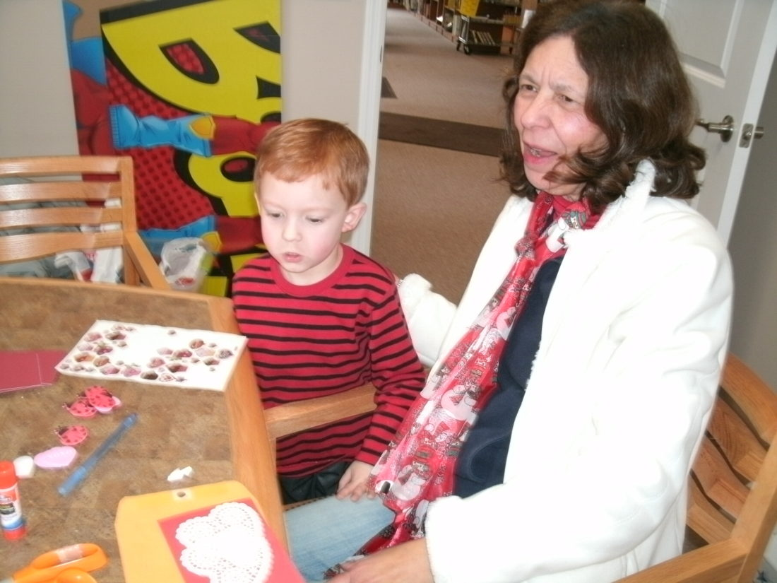 Kade Joseph Babcock and Diane Babcock working on valentine cards for veterans at the library.