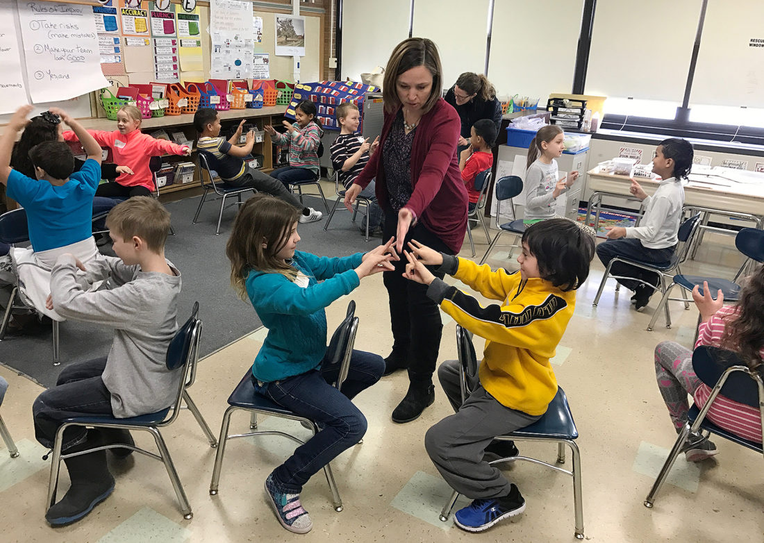 Kassie Misiewicz, Kennedy Center visiting artist, is pictured working with Ring Elementary School third graders in Elizabeth Johnson's class.