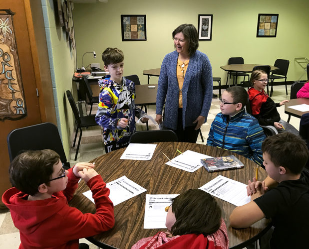Washington Middle School fifth graders, Kris Cruz, Nate Cornell, Eli Nowell, Conner Degnan, and Ethan Pumford work with School Secretary, Sandy Pratt, on an active listening role model exercise during one of the school's recent R-times.