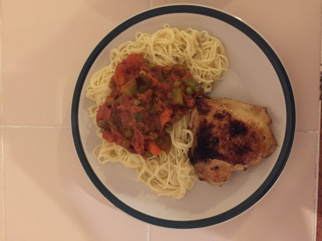 Spaghetti topped with Beans Stew compliments Roasted Chicken on this plate.