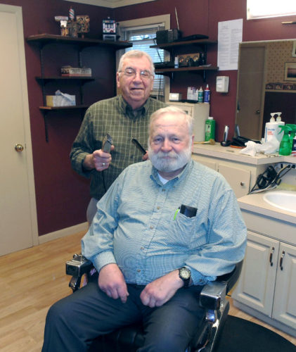 Vince's Barber Shop in Bemus Point will be celebrating 50 years of business this summer. Vince Alessi, owner, said he started cutting hair in 1960 alongside his uncles, Joe and Saro. Alessi is pictured with John Stahley, Bemus Point resident.  P-J photo by Jimmy McCarthy