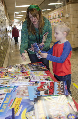 Ring Elementary School teacher, Wendy Rodgers helps kindergartner, Caleb Dykstra, pick out a free book as part of the school's Pick a Reading Partner Program.