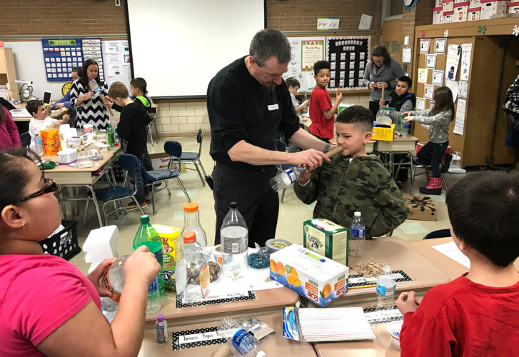 Ring Elementary School third grader, Alexis Morales DeJesus, tries out his recycled materials musical instrument with Kennedy Center Visiting Artist, John Bertles.
