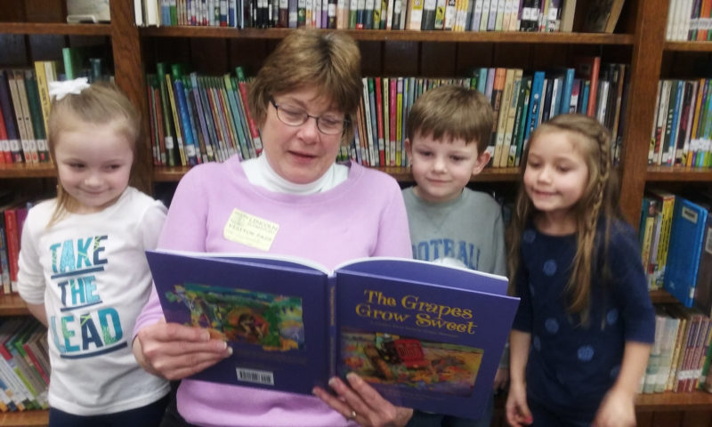 Lincoln Elementary School students, Raegan Karash, Zander Tibbetts and Maria Stone enjoy reading with Cornell Cooperative Extension volunteer Pat Martonis.