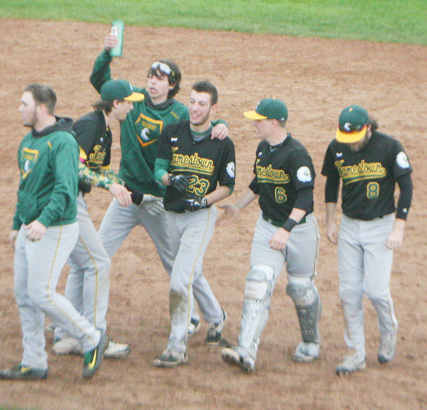 Jamestown Community College's Andrew Latona, No. 23, is mobbed by teammates after ripping a game-winning hit to send the Jayhawks to a 6-5 NJCAA Region 3 Division III baseball victory over Corning CC in the opener of a doubleheader Saturday afternoon at Diethrick Park.  P-J photo by Scott Kindberg