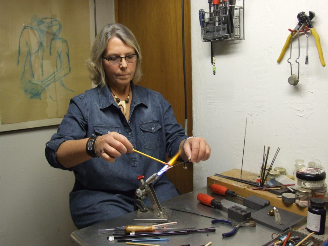 """Linda Mason makes beads using an oxygen propane torch and a glass rod. She describes it as """"painting with glass."""" Photos by Beverly Kehe-Rowland"""