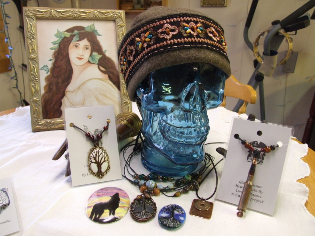 Linda Mason's display of a painting, wearable jewelry and a felted hat.