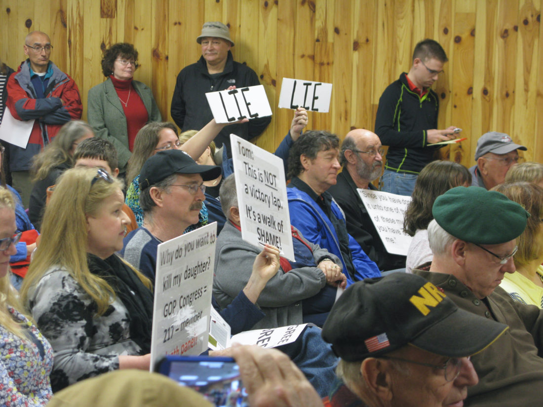 Several local residents hold up signs during Saturday's town hall meeting. Rep. Tom Reed said he supported the American Health Care Act that was passed in the House on Thursday.