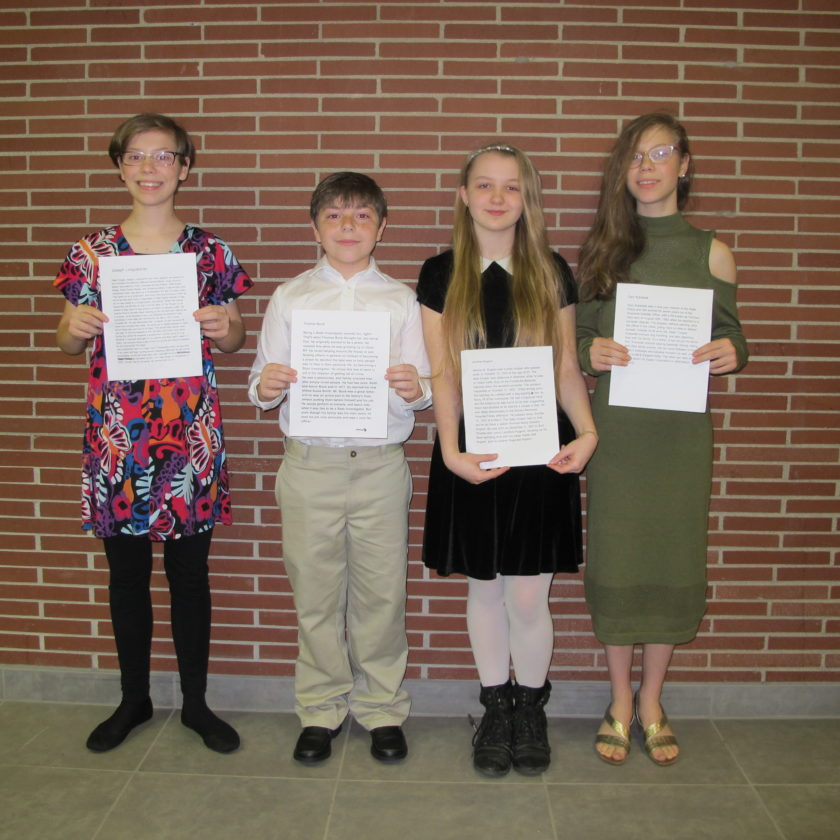 Persell eighth grade honor society members display the biographies they wrote honoring the event's four fallen officers. Pictured from left are Sydney Moss, Steven Dewey, Vanessa DeStevens and Alexandria Moss.  P-J photo by Remington Whitcomb