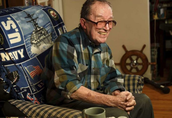 In this November 2014 photo, Lawrence J. Reilly Sr., a U.S. Navy veteran of World War ll and the Vietnam War, sits in the living room of his home in Syracuse, N.Y. He and his 20-year-old son Lawrence J. Reilly Jr. were serving together on U.S. Navy destroyer Frank E. Evans when the ship was cut in half in a collision with the aircraft carrier HMAS Melbourne of the Royal Australian Navy during joint maneuvers in the South China Sea. Seventy-four sailors died but the Pentagon has rejected a longstanding request from survivors of the disaster to add the names of their fallen comrades to the Vietnam Veterans Memorial in Washington, D.C., saying the accident occurred outside the Vietnam combat zone. AP photo